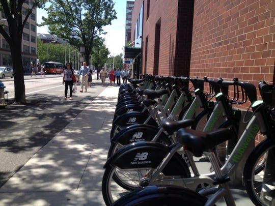 Free bicycles are available to pedestrians in Cambridge, Mass., which is quickly becoming the hub for pharmaceutical research.