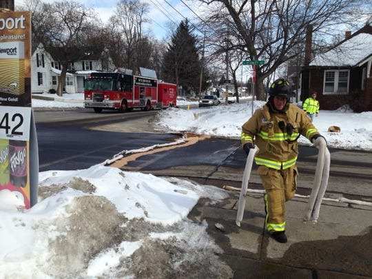 A firefighter carries absorbant material after a gasoline spill on East Emmett Street on Monday afternoon.