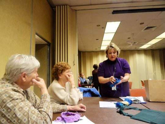 Librarian Amy Atzert, standing, shows her crochet work to some of the people who came to our knitting workshops at the Bridgewater Library in December.