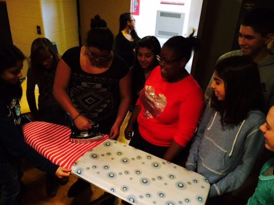 Students iron clothes for Comet's Closet at Sabish Middle School.