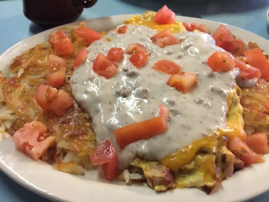 """The """"Trash"""" is a hash brown with meats, eggs and cheese, served with biscuit gravy over top."""