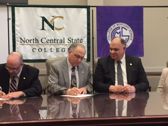 Students at North Central State College may now work toward an associate's degree in mortuary science. At left, Gregg Busch, dean of liberal arts at NCSC, Dorey Diab, president of NCSC, and Eugene Kramer, president of the Cincinnati College of Mortuary Science, sign the new articulation agreement between the two institutions.