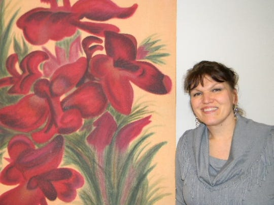 Artist Bridget Reil poses next to her painting, Red Orchid.