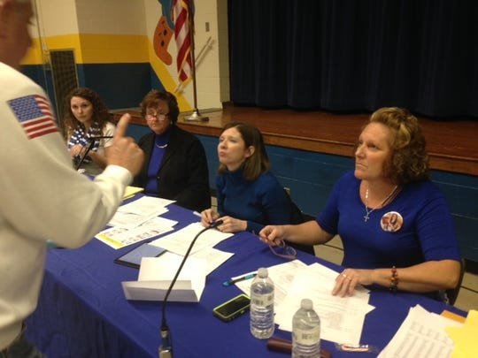 A patron questions Union School board members Christina Ogden, Christa Ellis and Teresia Green, left to right. Their attorney is second from left.