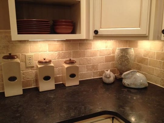 A leathered granite countertop is accented with a natural beige stone tile backsplash.