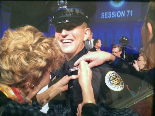 Michael Petrina's mother, Joyce, pins on his badge