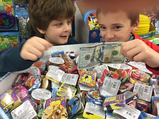 Connor Oertel, right, was with his friend Zane Zaminski when he found a $100 bill signed by Benny in this bin at the Dollar Tree in Keizer. They plan to pay it forward by buying toys and donating them to a local organization. Their moms are matching the amount so they will have $200 to spend.