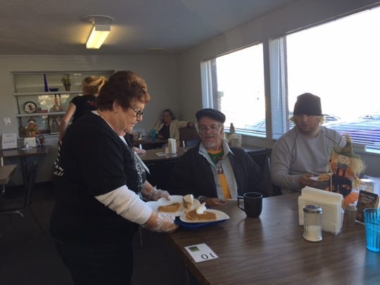 Volunteer LaVerna Horton serves pumpkin pie to guests at a Thanksgiving meal provided by the Bread of Life Community Soup Kitchen in Cedar City Wednesday, Nov. 26, 2015.