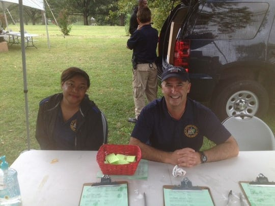 Sarita Wright, on the day before she died, attending the Department of Justice's Community Resource Fair at Christina Park. To her left is Deputy Attorney General John Grimm.