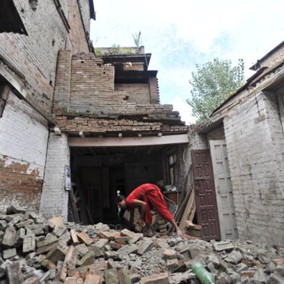A Nepalese resident clears rubble from collapsed and