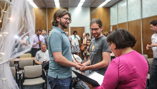 Craig Bowen (left), Jake Miller, become the first gay couple married by Marion County Clery Beth White, at the City County Building in Indianapolis.