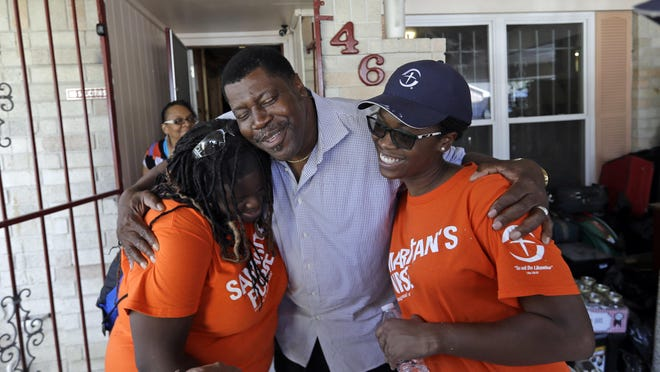 In this Nov. 17, 2017 photo, George Dorsey, center, hugs Samaritan's Purse volunteers, Nikki Moore, left, and Samantha Roundtree, who are helping rebuild his hurricane-damaged home in Houston. Dorsey usually hosts a large Thanksgiving dinner for family but is making other arrangements this year as they continue to recover from the storm damage.