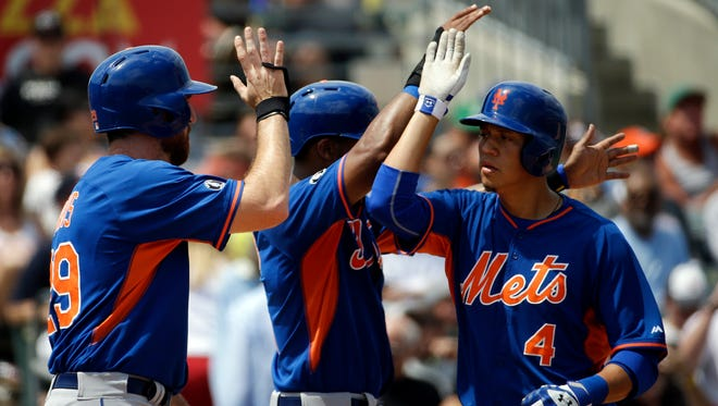 The Mets' Wilmer Flores, right, high-fives teammates Chris Young, center, and Ike Davis after hitting a three-run home run in the fourth inning of an exhibition game against Miami on Saturday.