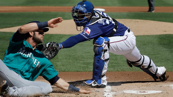 Texas catcher A.J. Jimenez tags out the Mariners' Mitch Haniger at the plate in the first inning Sunday in Surprise, Ariz.
