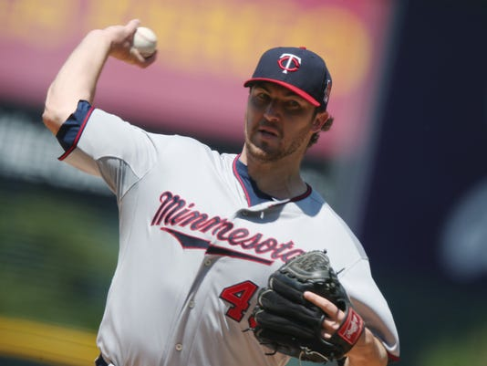 Minnesota Twins starting pitcher Phil Hughes works against the Colorado Rockies in the first inning of an interleague baseball game in Denver on Sunday, July 13, 2014. (AP Photo/David Zalubowski)