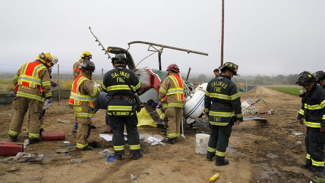 Firefighters from the Salinas Fire Department and Monterey County Fire Department work a helicopter crash scene off Blanco Road in Salinas on Saturday morning.