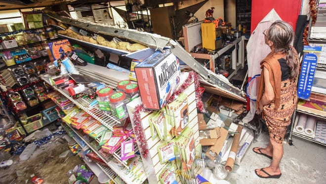 School Essentials store owner Rose Santo Tomas surveys the damage to her business after emergency personnel responded to a report of an explosion and fire at the Oka Commercial Center in Tamuning on Wedneday, Dec. 14. A wall shared with her store and an adjoining room, collapsed into her space and onto one of her employees working behind the counter.