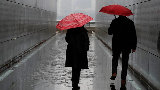 FILE - In this Tuesday, Jan. 17, 2017, file photo, a couple walks through the Empty Sky Memorial during a rainy day at Liberty State Park,  in Jersey City, N.J. An age difference in your relationship doesn't just mean your favorite bands are from different decades. Even a small difference in years between two people can affect when you retire, how much you need to save and how those savings are invested.