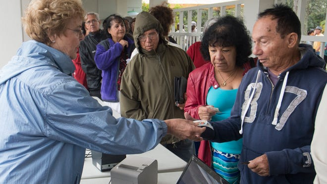 St. Matthew's House volunteer Diane Demott, left, gives a voucher to Collier County residents Ovidio and Juana Carrazainya The voucher will be exchanged for a turkey. More than 150 people waited in line to get the voucher.