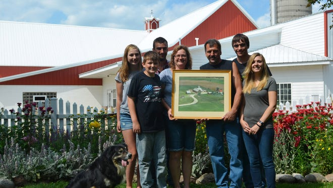 The Rahmlow family poses with an old aerial picture of their farm in front of their home on July 18. The family, left to right from the back: Kyra, Jarrod, Trent, Kaden, Judy, Mark, Jena