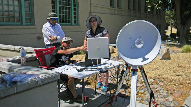 "New Mexico State University astronomy Ph.D. student Sten Hasselquist, center, chemical engineering student Norann Calhoun, right, and Paulo Oemig, New Mexico Space Grant Consortium senior research scientist, work with the ground station equipment in preparation for the launch of a high-altitude balloon as part of the ""Great American Eclipse"" Aug. 21. The ground station will enable the NMSU team to track the balloon and transmit the video feed."