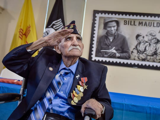 In a Sept. 23, 2017 photo,  Joe Romero salutes General Kenneth A. Nava after he is presented with the Bronze Star as well as other medals in Albuquerque, N.M. Romero is a Bataan Death March survivor. He was surrounded by his family Saturday as he also celebrated his 97th birthday at the New Mexico Vietnam Veterans Visitor Center in Albuquerque.