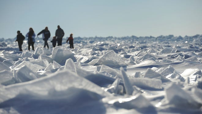 A family explores fields of ice on frozen Lake Michigan in South Haven, Mich., Sunday, March 8, 2015.