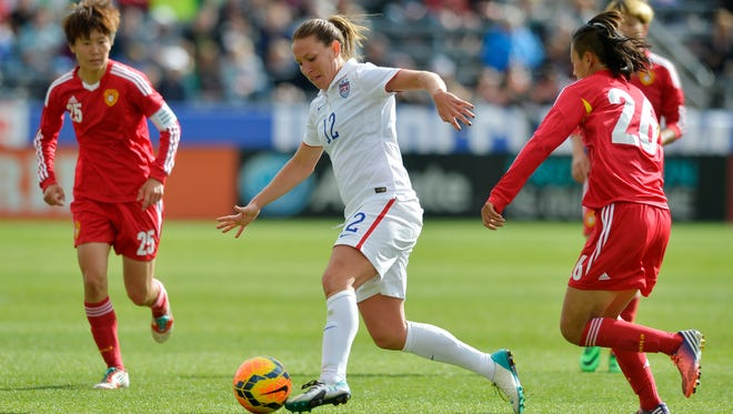 U.S. midfielder Lauren Holiday (12) moves the ball between China's Zhang Rui (25) and Li Dongna (26) during the second half of an international friendly soccer match  in Commerce City, Colo., on Sunday, April 6, 2014.