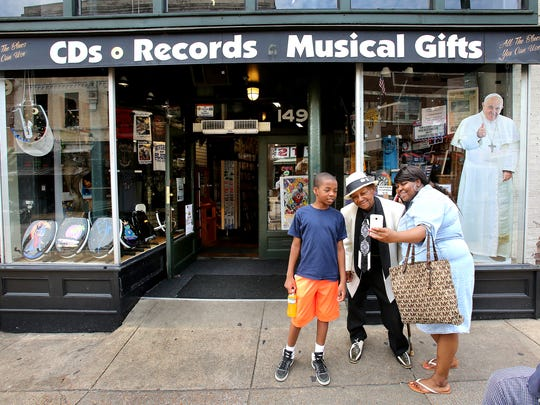 "While on a walking tour of Beale Street, Kishana Houston (right) and her nephew Cameron Houston stop in to shop at Memphis Music and take a selfie with the ""Godfather of Blues"" Clyde Hopkins."