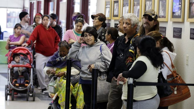 People line up at a food pantry at Sacred Heart Community Service in San Jose, Calif.