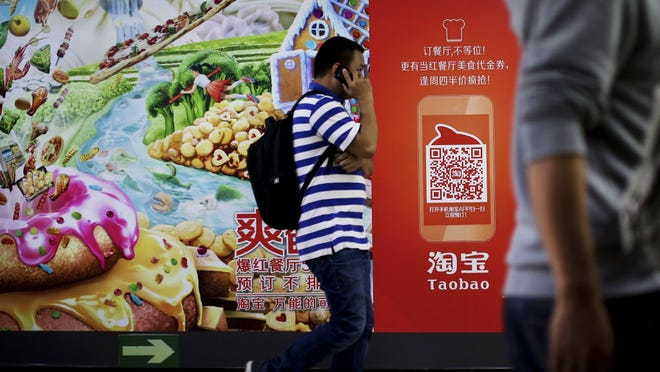 A Chinese man talks on a mobile phone as he walks past a Taobao's mobile app advertisement billboard on display inside a subway station in Beijing, China Wednesday, Sept. 17, 2014. China's Alibaba Group is seeking to raise up to $24.3 billion in its upcoming IPO ó an amount that would be the most raised by a company in a stock market debut. Taobao is one of the popular services from Alibaba Group. (AP Photo/Andy Wong) ORG XMIT: XAW101