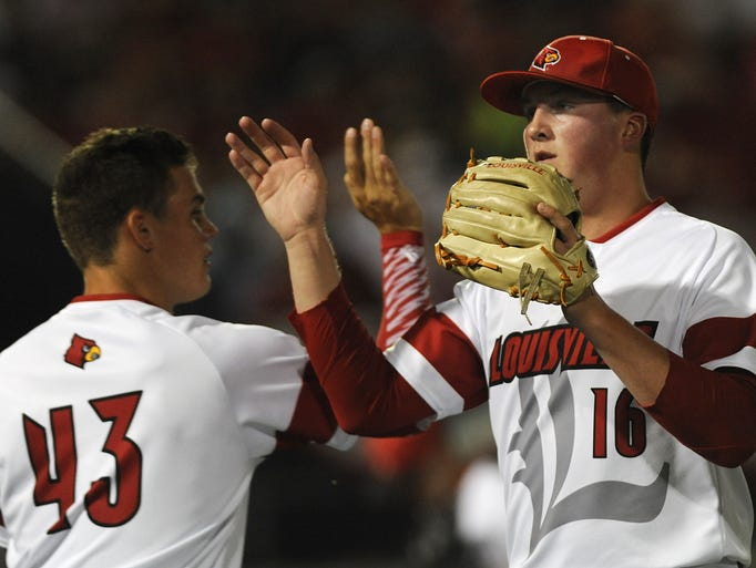 Louisville pitcher Kyle Funkhouser (right) receives a high-five from Zack Burdi (left) after closing out Kent State in the first inning on Friday during the Louisville Regional at Jim Patterson Stadium. May 30, 2014