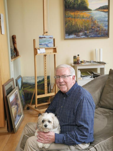 Architect and artist Paul R. Schultz holds Easel, a teddy bear ??? half bichon and half Shih Tzu.