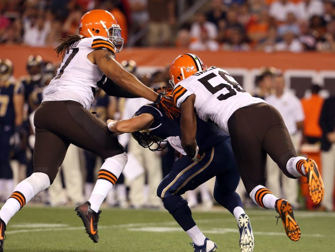 Cleveland Browns inside linebacker Karlos Dansby (56) and outside linebacker Jabaal Sheard (97) sack St. Louis Rams quarterback Austin Davis (9) during the second quarter at FirstEnergy Stadium.