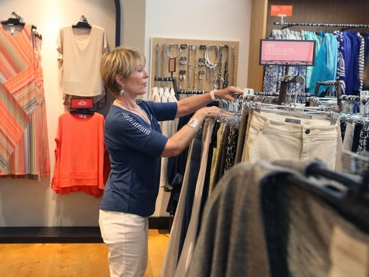 Helen Polek, of Chicos, puts clothing back on the rack while working at the Coconut Point Mall location on Thursday.