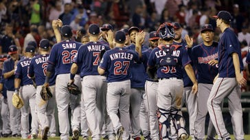 Minnesota Twins relief pitcher Brandon Kintzler (27) and second baseman Brian Dozier (2) celebrate after the Twins defeated the Boston Red Sox 2-1 on Friday at Fenway Park in Boston.