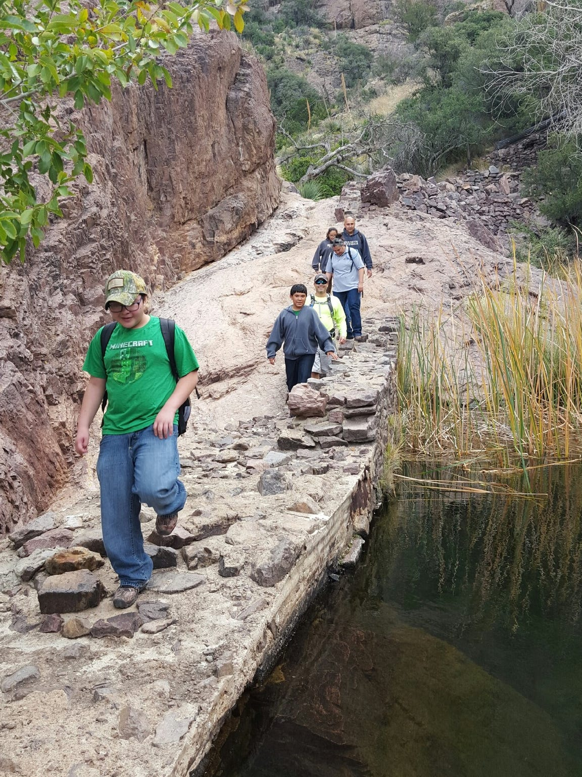 Kids hike a trail in Dripping Springs Natural Area as part of the City of  Las Cruces Parks and Recreation Department's Youth Plus 1 Hiking Program in 2016.