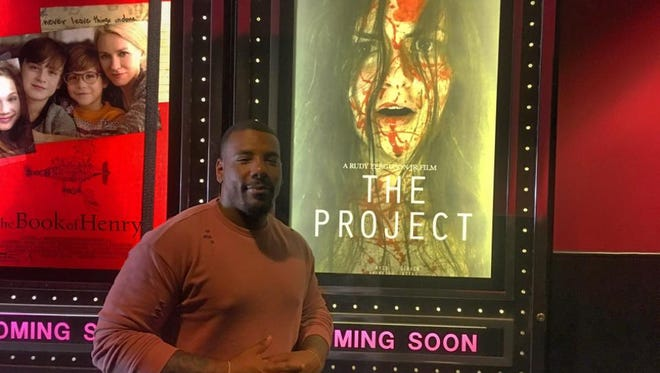 """Rudy Ferguson Jr. stands in front of """"The Project"""" movie premiere poster."""