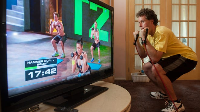 Michael Nasuti, 33, of Mount Laurel performs a hammer curl and a squat as he does the FOCUS T25 workout in his home.