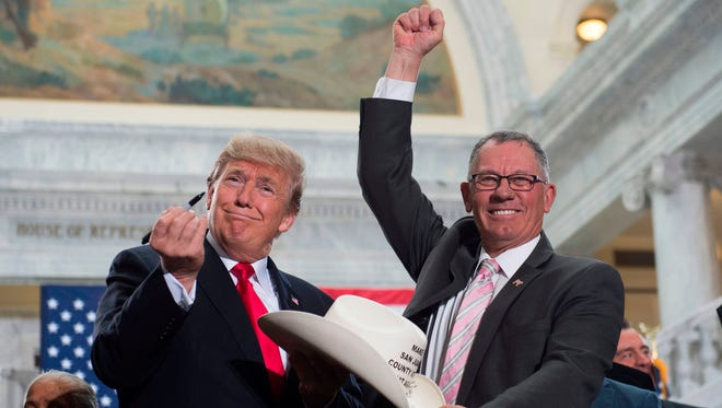 US President Donald Trump holds up a pen after signing the hat of Bruce Adams, Chairman of the San Juan County Commission, after signing a Presidential Proclamation shrinking Bears Ears and Grand Staircase-Escalante national monuments at the Utah State Capitol in Salt Lake City, Utah, December 4, 2017.