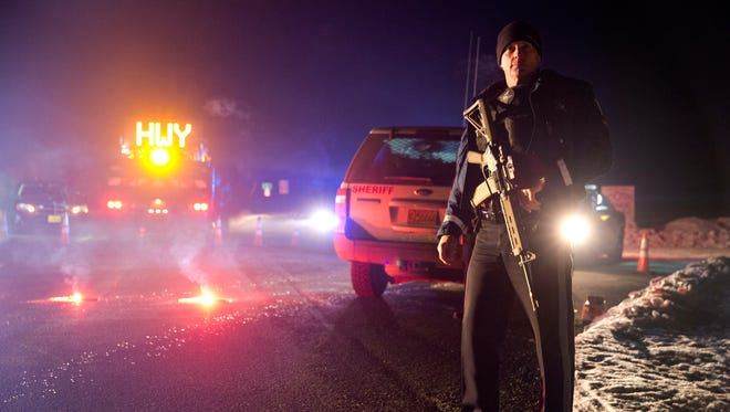 Sgt. Tom Hutchison stands in front of an Oregon State Police roadblock on Highway 395 between John Day and Burns by Oregon State police officers Tuesday, Jan. 26, 2016. Authorities say shots were fired Tuesday during the arrest of members of an armed group that has occupied a national wildlife refuge.