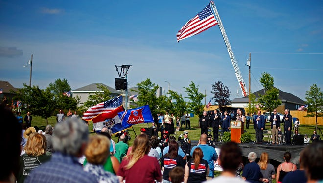 Attendees sing the national anthem during a ceremony in Cunningham Park in Joplin, Mo., on Sunday, May 22, 2016, marking the fifth anniversary of the EF5 tornado that hit the city in 2011.