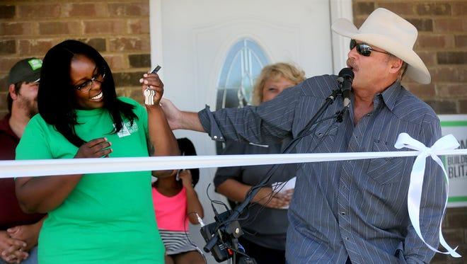 Country Music star Alan Jackson hands the keys over to Keosha Hendricks during the Habitat for Humanity Home Builders Blitz, in La Vergne Friday..