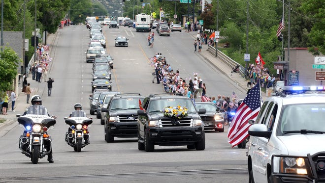 Durango honors Marine Capt. Jeff Kuss as the motorcade escorting his remains to Greenmount Cemetery makes its way down Main Avenue on Saturday, June 11, 2016, in Durango, Colo. Kuss died on June 2 when his plane crashed during a Blue Angels practice exercise for an air show in Tennessee.