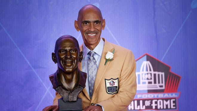Former Indianapolis Colts coach Tony Dungy poses with his bust during the NFL Hall of Fame Enshrinement Ceremony at Tom Benson Hall of Fame Stadium in Canton, Ohio, on Aug. 6, 2016.