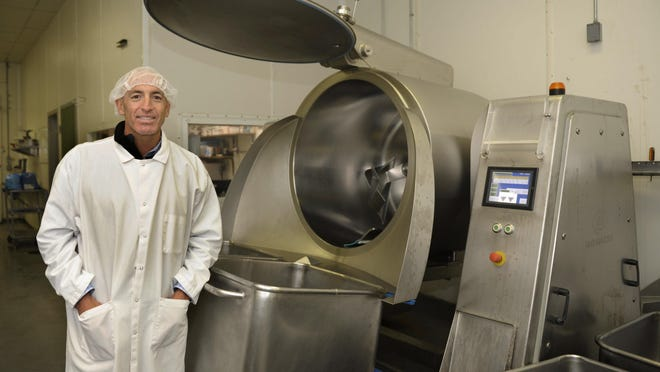 Chris Flocchini, the president/CEO of Flocchini Family Provisions in Carson City, takes a moment beside the vacuum tumbler used to marinate meat. The tumbler is among the equipment introduced to the factory after the Flocchinis purchased it from its longtime owners in 2015.