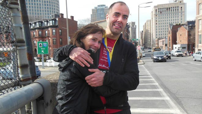 Neenah's Linda Witt hugs her son, Bill Tanguay, while reuniting on the streets of Boston after they were separated for about two hours, following the bombings during the Boston Marathon in April 2013.