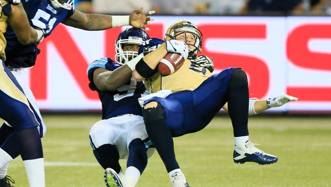 Toronto Argonauts defensive lineman Tristan Okpalaugo (91) sacks Winnipeg Blue Bombers quarterback Drew Willy (5) during the first half at Rogers Centre in 2014.