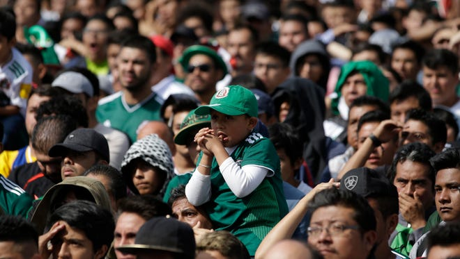 Worried Mexico soccer fans watch a live telecast of the group F match between Mexico and Sweden, at the 2018 soccer World Cup, in Mexico City's main square, the Zocalo, Wednesday, June 27, 2018.
