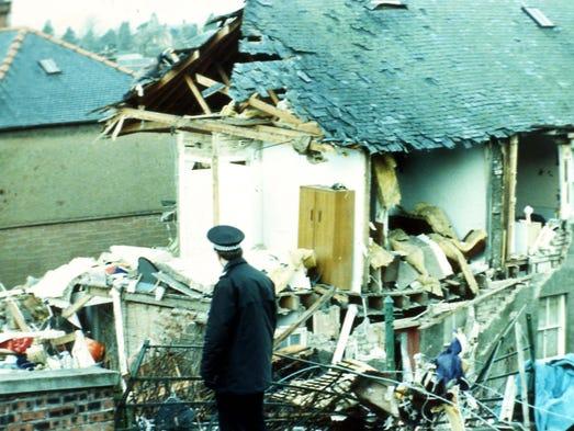 A police officer walks past the damage in Lockerbie,